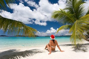 woman with santa hat on tropical beach for christmas